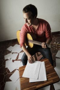 A young man writing songs at home.
